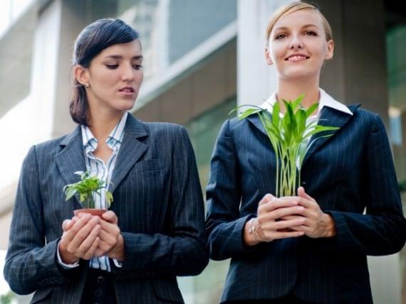 Foto de duas mulheres com plantas na mão, uma delas está com uma planta bonita e crescida, a outra está com uma planta pequena, e olha pra outra com inveja!